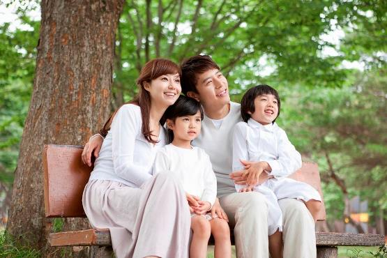 a family sitting on a bench in the park